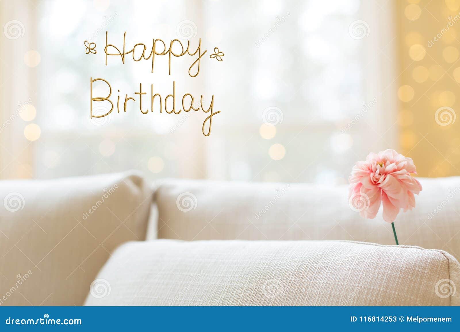 Messaggio di compleanno con il fiore in sofà interno della stanza