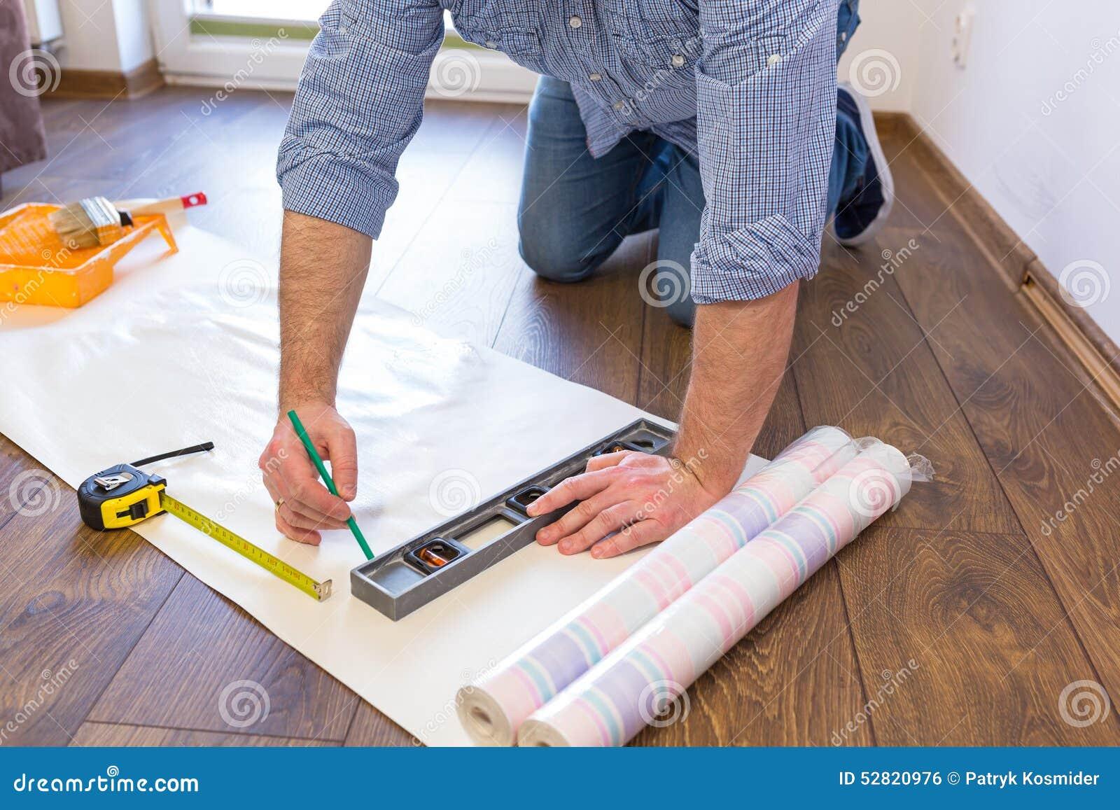 messende tapete des heimwerkers zu schneiden stockfoto - bild von