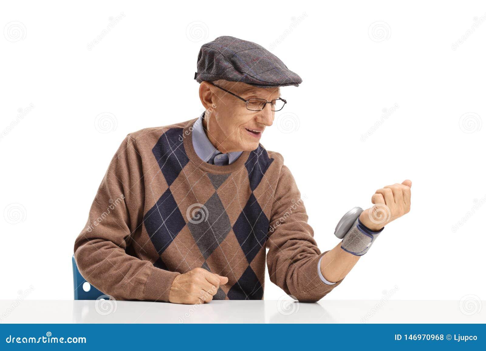 Messender Blutdruck des älteren Mannes mit einem Handgelenkgerät