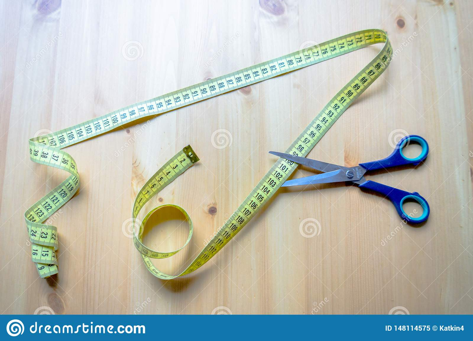 Messendes Band und Scheren, die auf einem Holztisch liegen