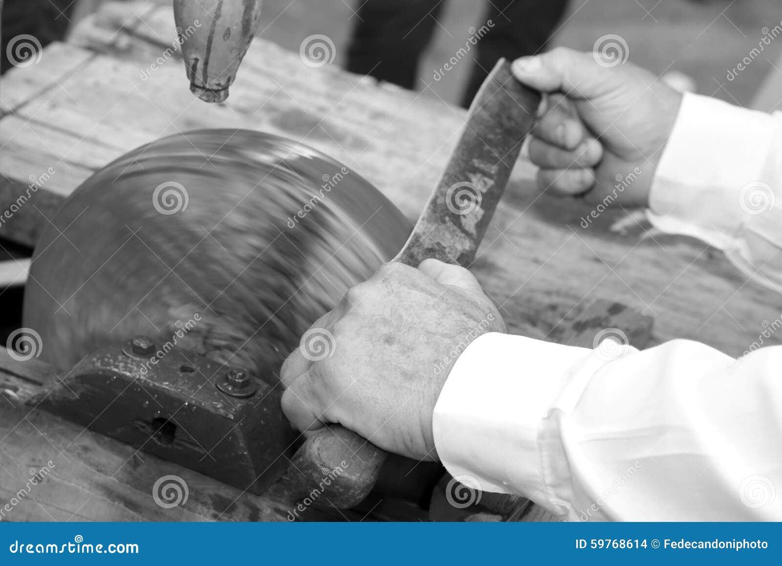 Messenslijper terwijl het scherpen van het blad van het mes op l