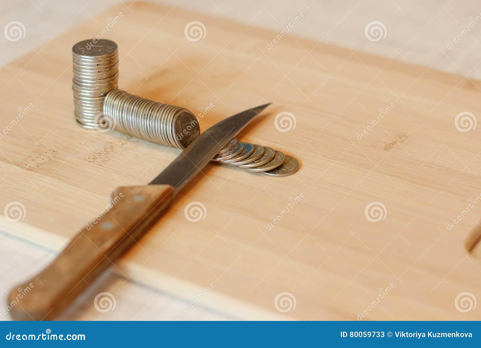 Messer, das einen Stapel der Münze schneidet Konzept von Etatverkürzungen, Einsparungen, r