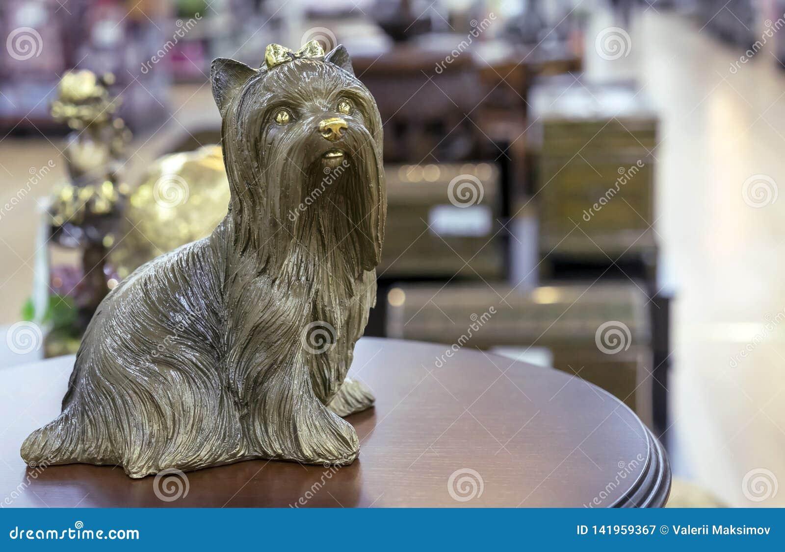 Messingsbeeldje van Yorkshire Terrier op een ronde houten lijst