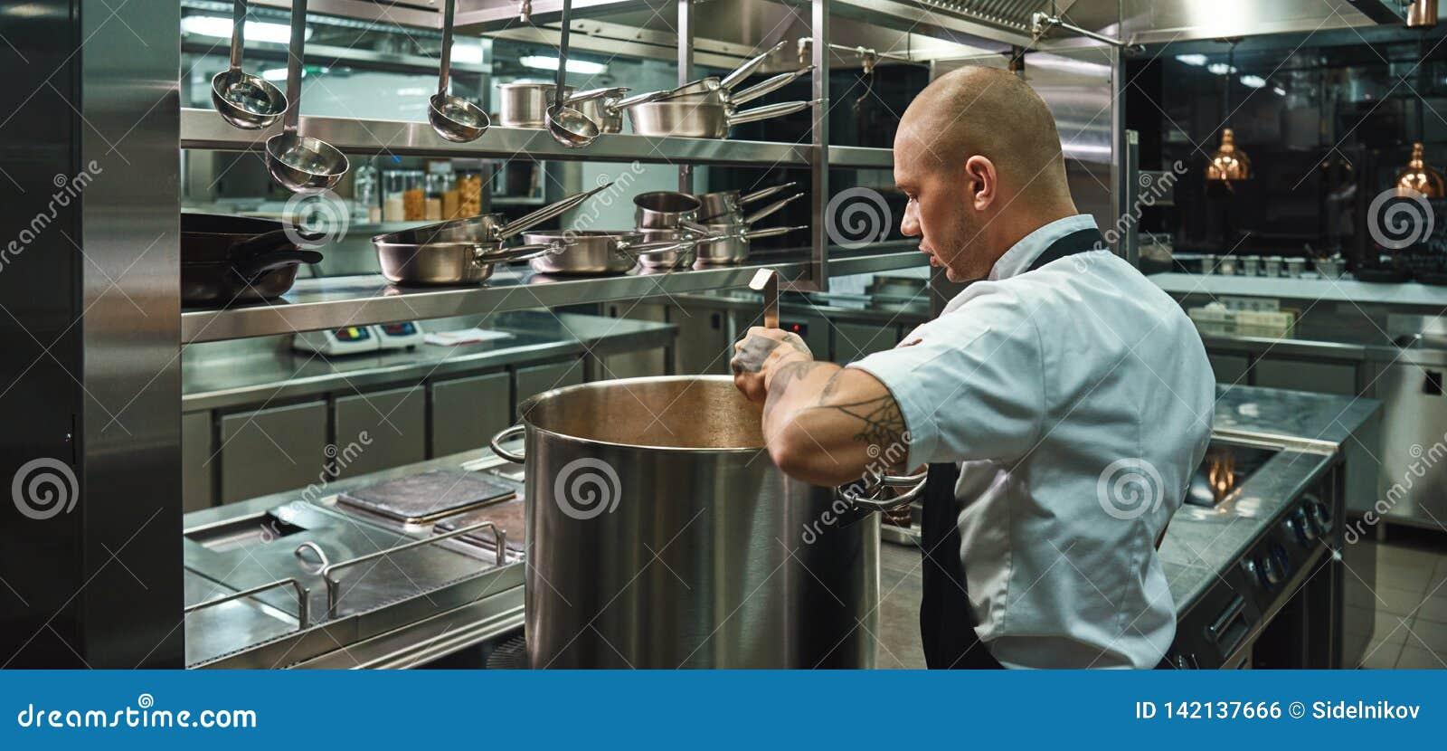 Messo a fuoco sul suo lavoro Vista laterale di giovane cuoco unico famoso con i tatuaggi sulle sue armi che cucina una minestra i