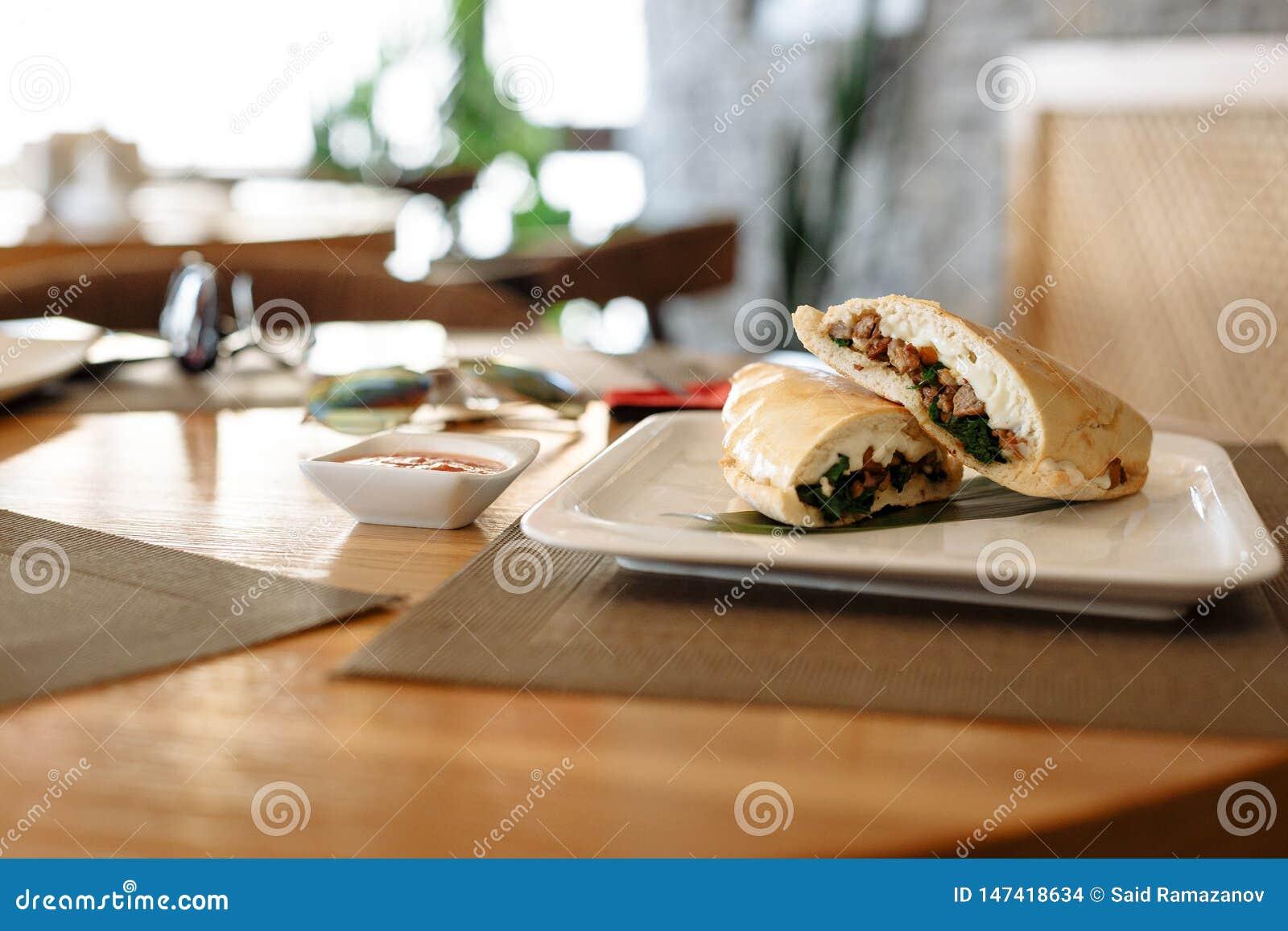 Metà della pizza di Calzone sullo strato di bambù in piatto quadrato sulla tavola di legno