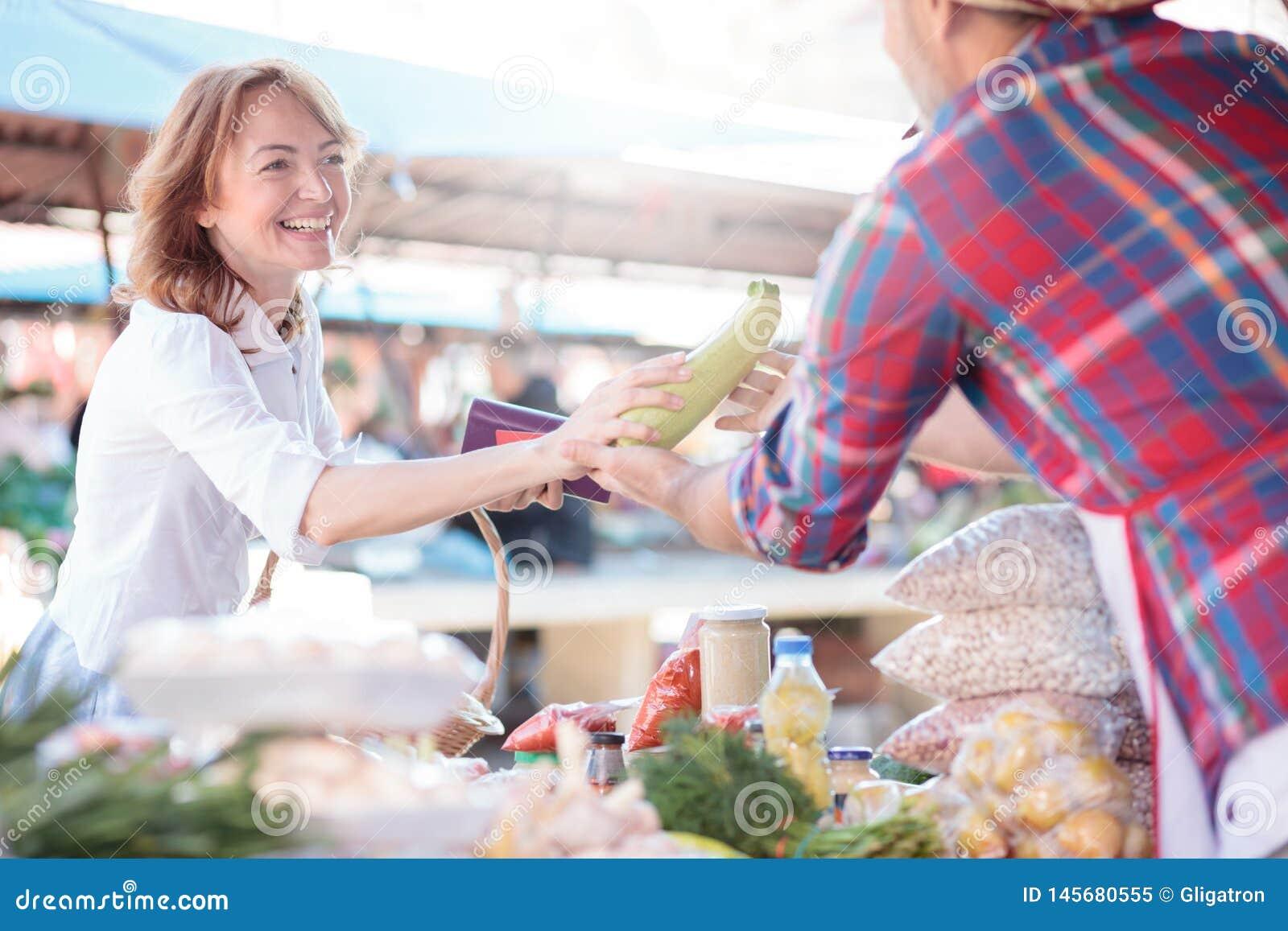 Metà di acquisto sorridente felice della donna adulta per le verdure organiche fresche in un mercato, portante un canestro