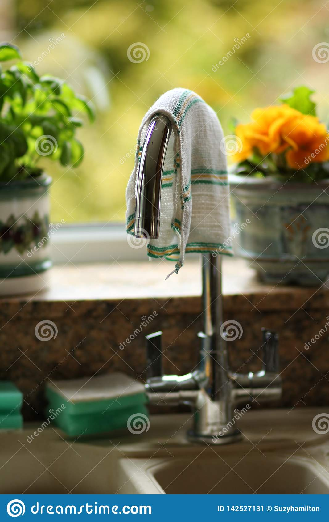 Metálico da torneira da cozinha unido acima do dissipador em um fim da cozinha da casa acima