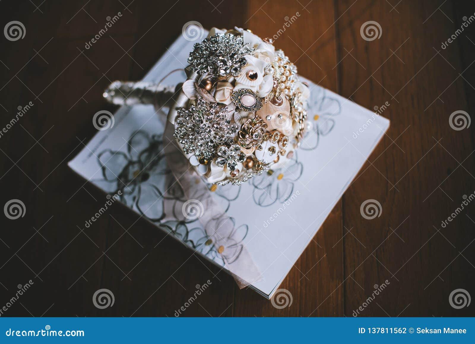 Met de hand gemaakt brocheboeket op het witte boek op houten vloer