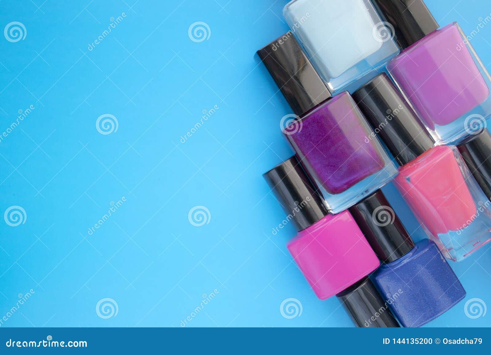 Met le vernis à ongles en bouteille Un groupe de manucures lumineuses sur un fond bleu Avec l espace vide du côté gauche