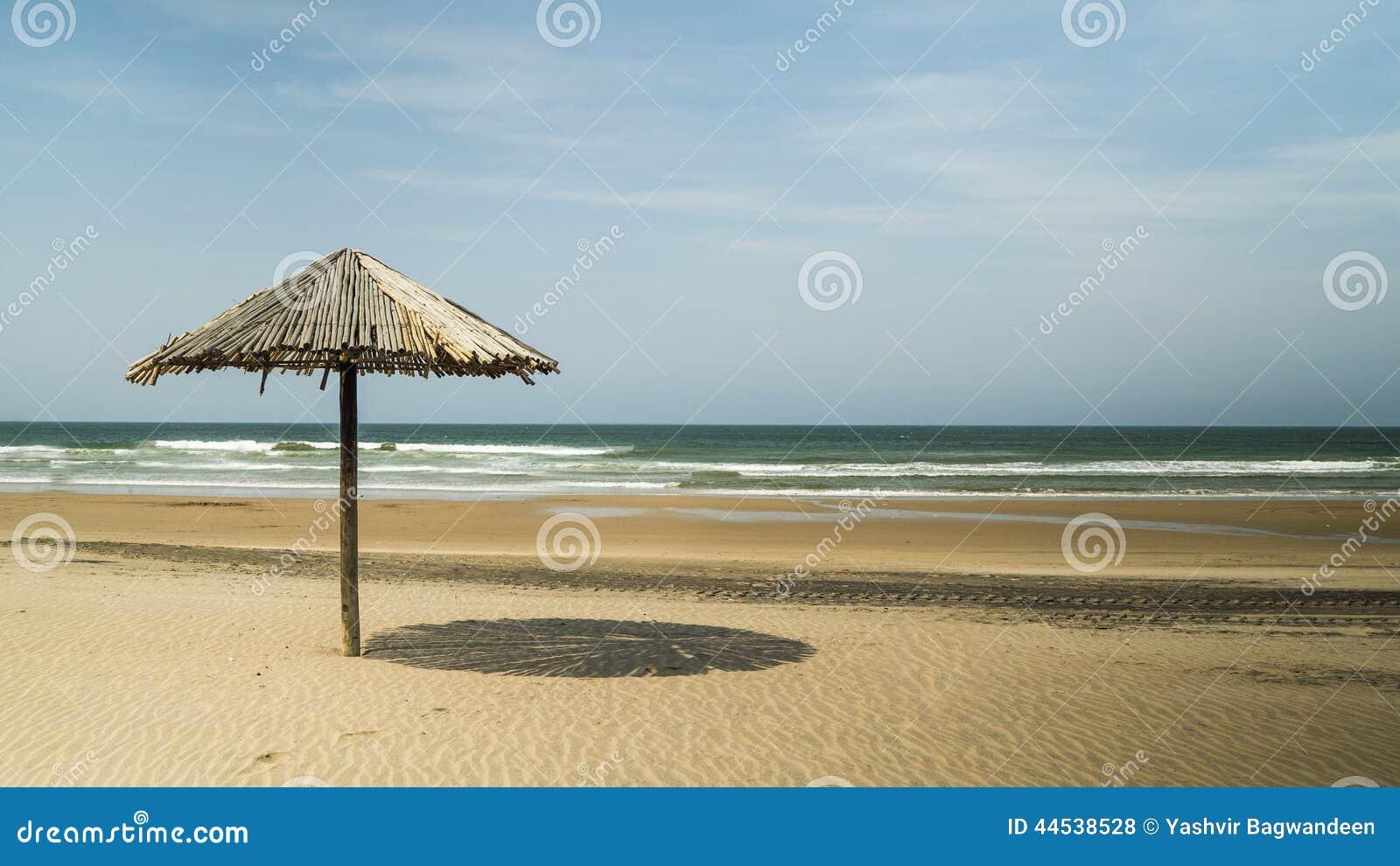 Met stro bedek paraplu op het strand stock foto afbeelding