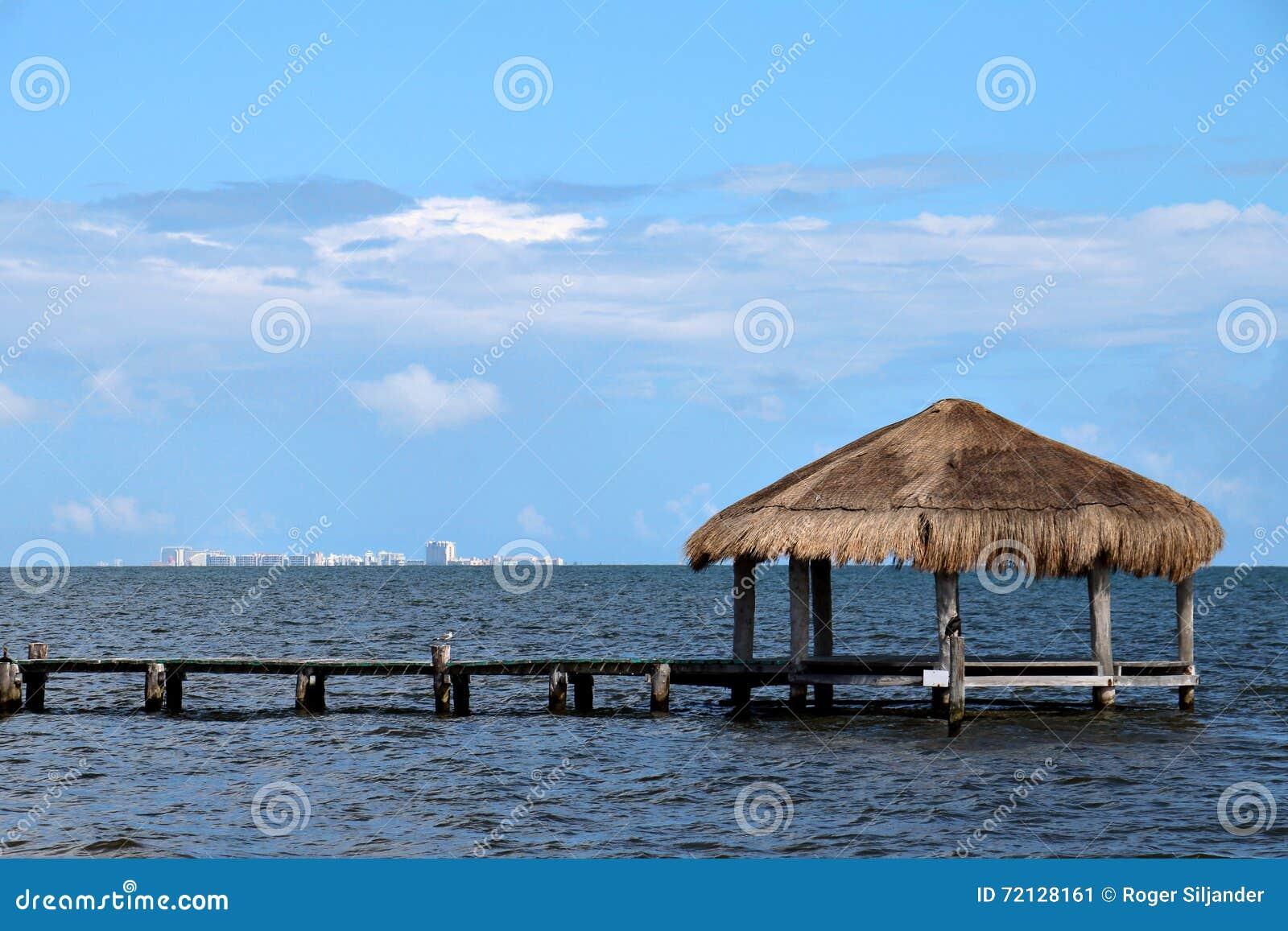 Met stro bedekte cabana op dok met cancun op de horizon stock