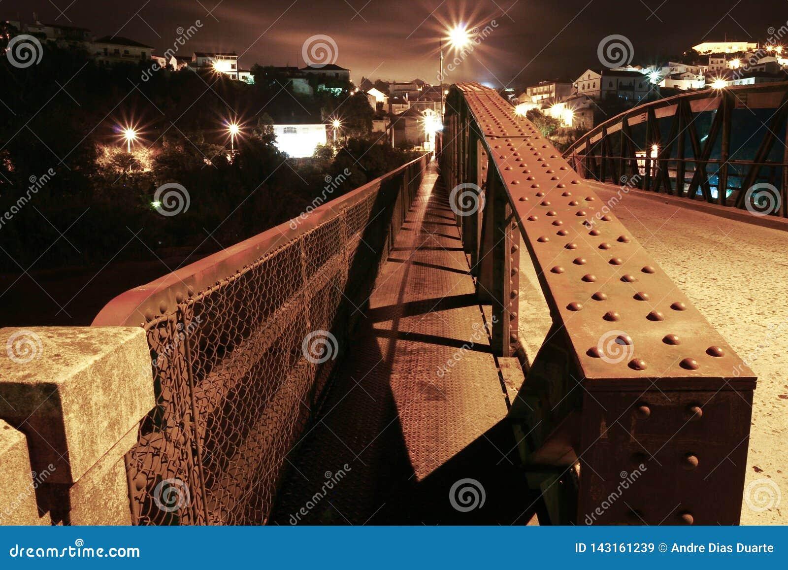 Metaalbrug met kleine stad aan de andere kant