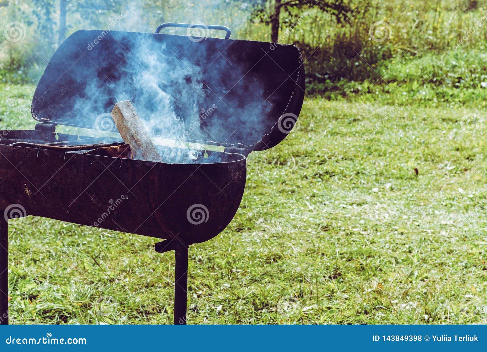 Metaalkoperslager met brand en rook bij zonnige de zomerachtergrond Voorbereiding van houtskool van hout voor een shishbarbecue o