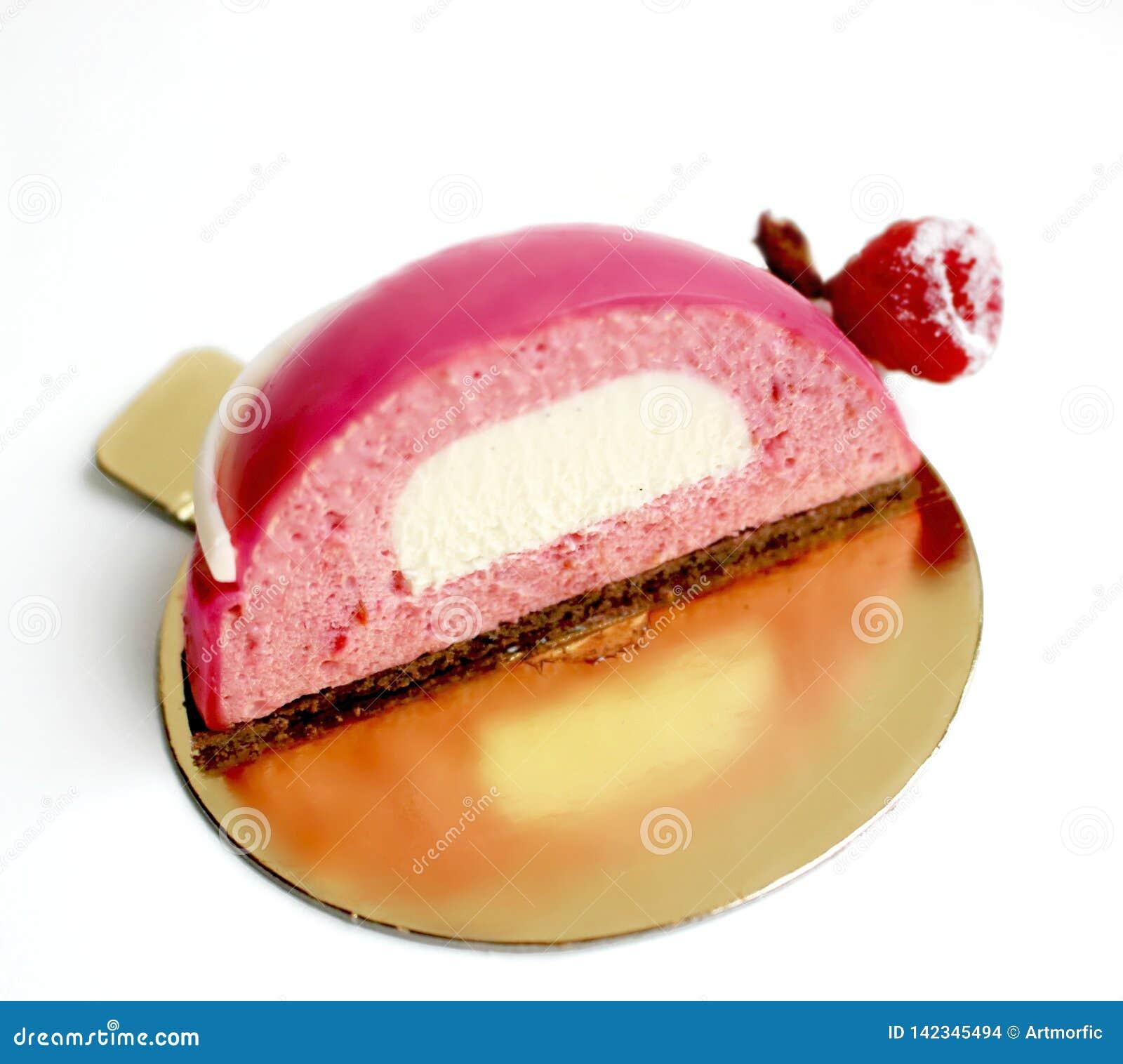 Metade cor-de-rosa da sobremesa da musse da framboesa com inserção branca da baunilha na pousa-copos dourada