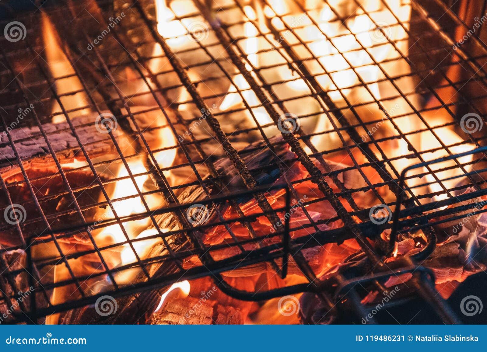 Metal сеть над древесиной тлеющих углей угля огня горящей в гриле барбекю на