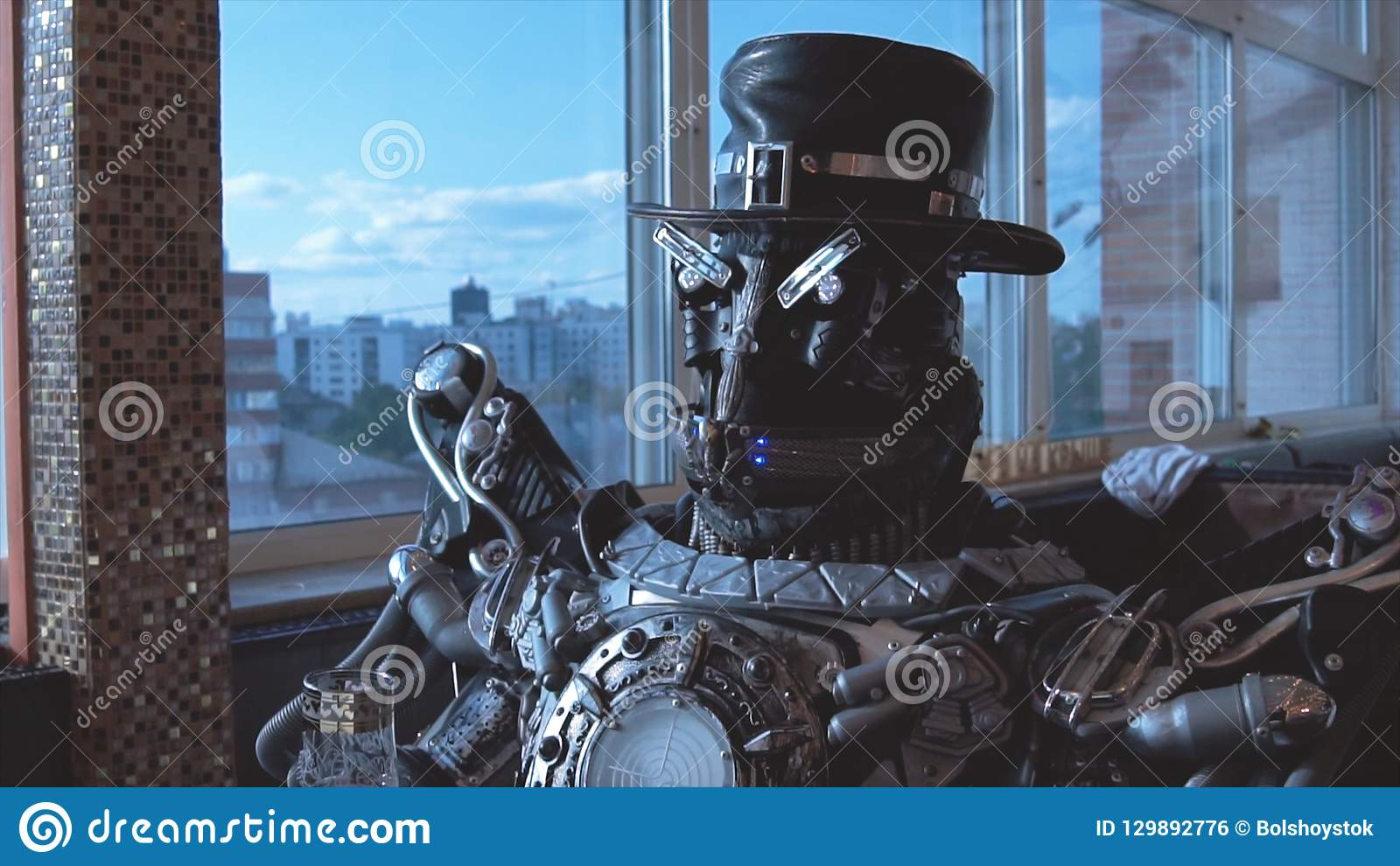 Metal android sitting at table in restaurant with glass of wine on background of view of high-rise buildings of city