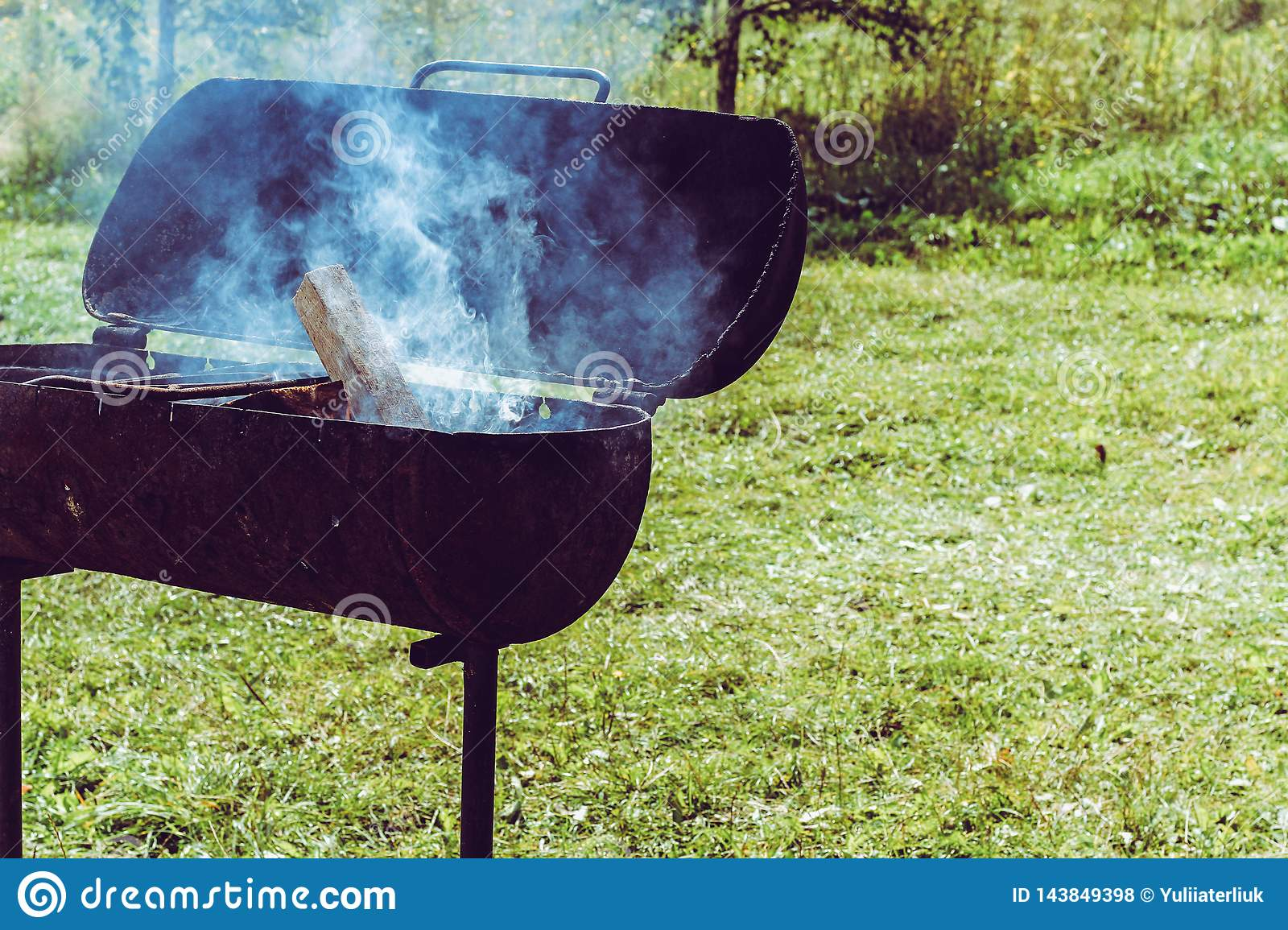 Metal brazier with fire and smoke at sunny summer background. Preparation of charcoal from wood for a shish barbecue on a rusty