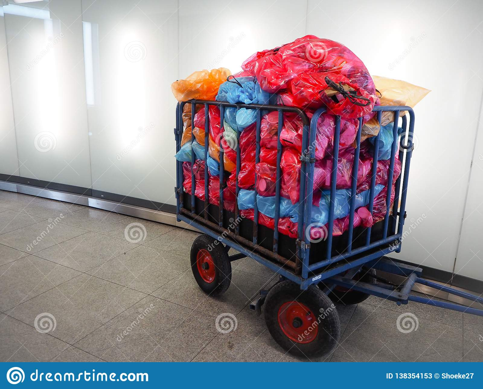 Metal cart for waste collection with a large pile of colorful plastic bags filled with sorted waste ready