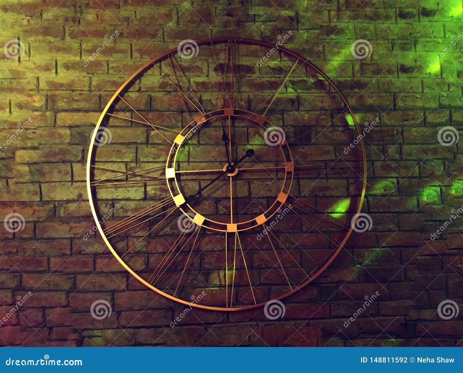 A metal clock on a brick wall