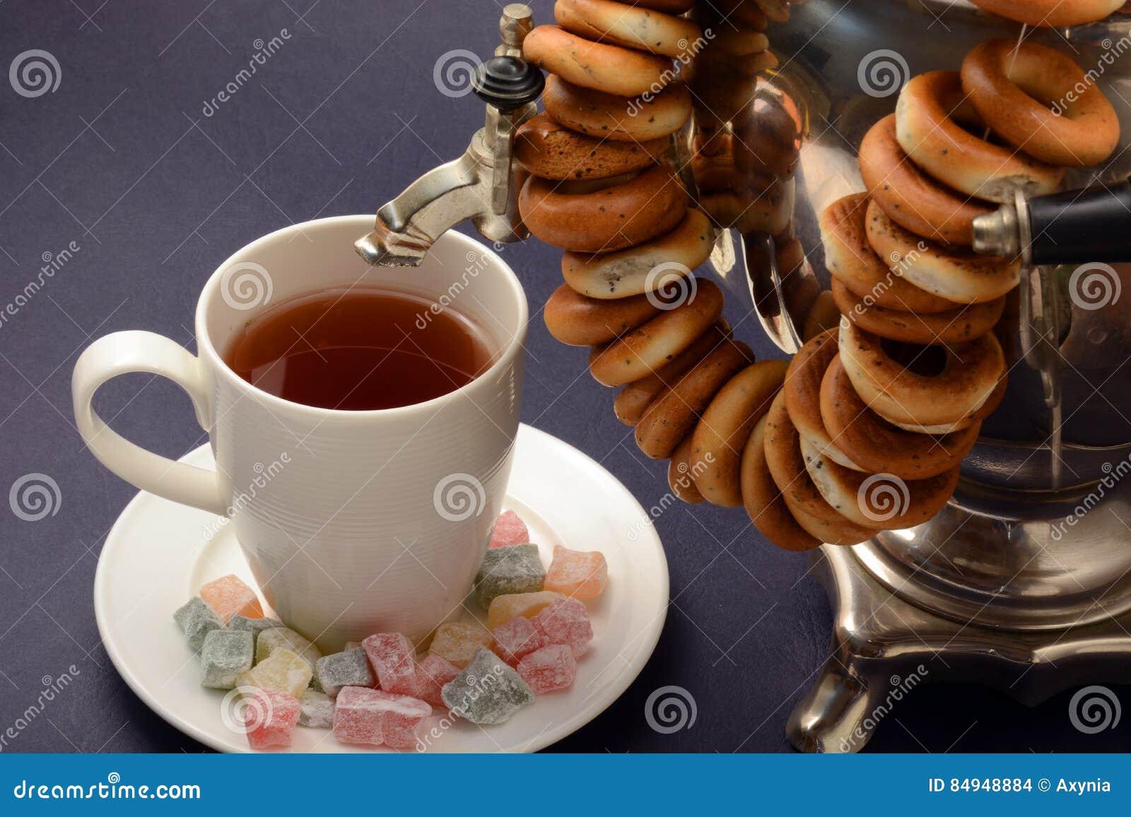 Metal del vintage del samovar del té negro en fondo oscuro con placer turco de los panecillos