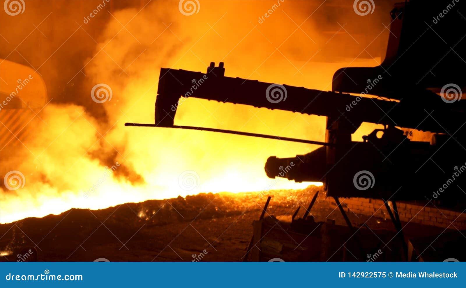 Metal fundido que vierte del mecanismo especial, concepto de la metalurgia Acero fundido que fluye en canal inclinado metalúrgico