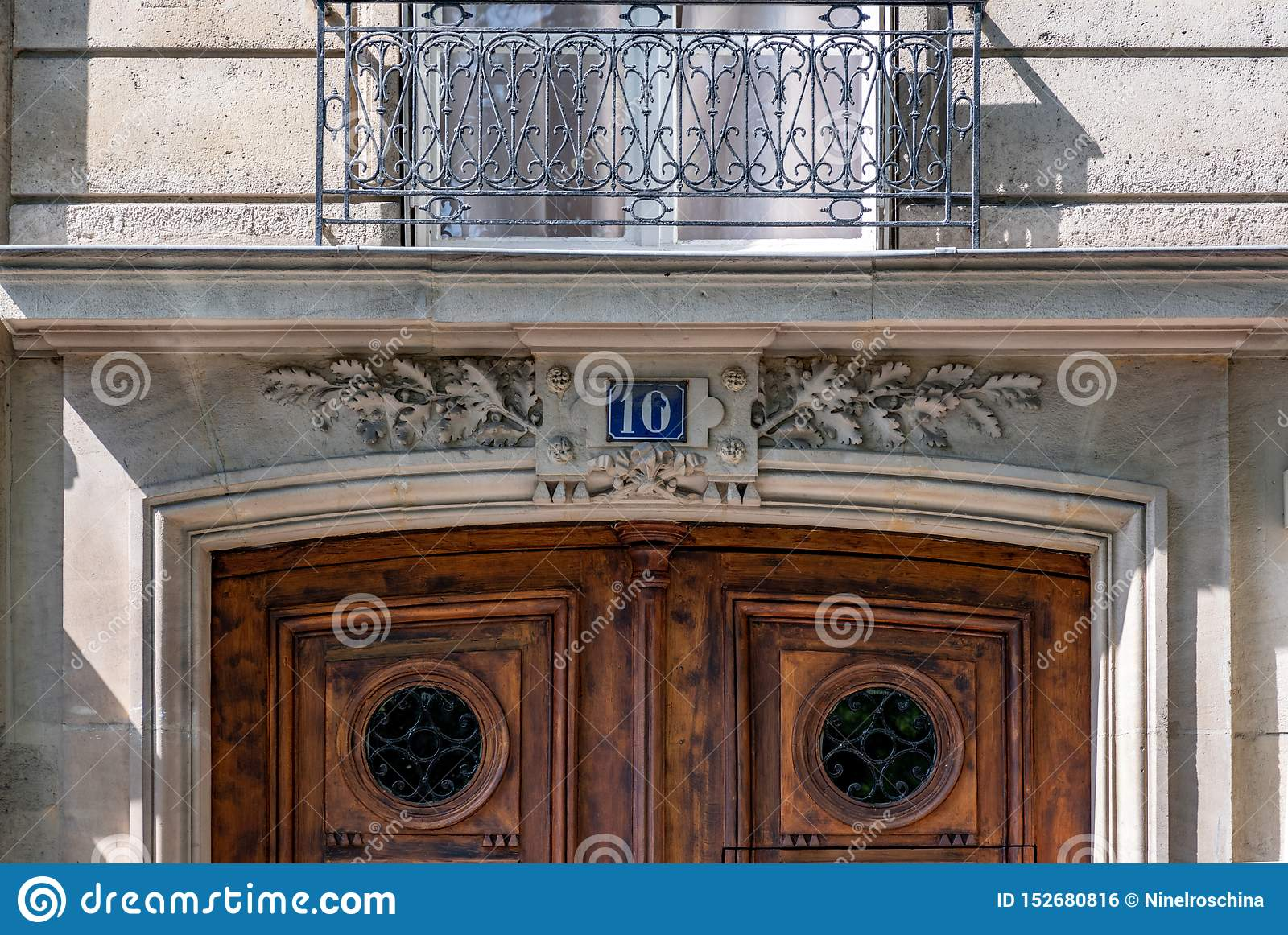 Metal Gratings On Window Above Top Part Of Vintage Wooden Door With Framed Panels And Round Windows Protected By Ornate Lattice Stock Photo Image Of Facade Baroque 152680816