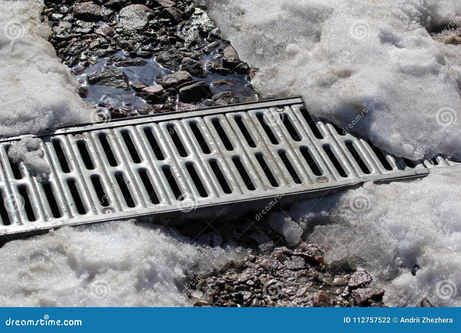 Metal la rejilla del drenaje del agua debajo de la nieve de fusión