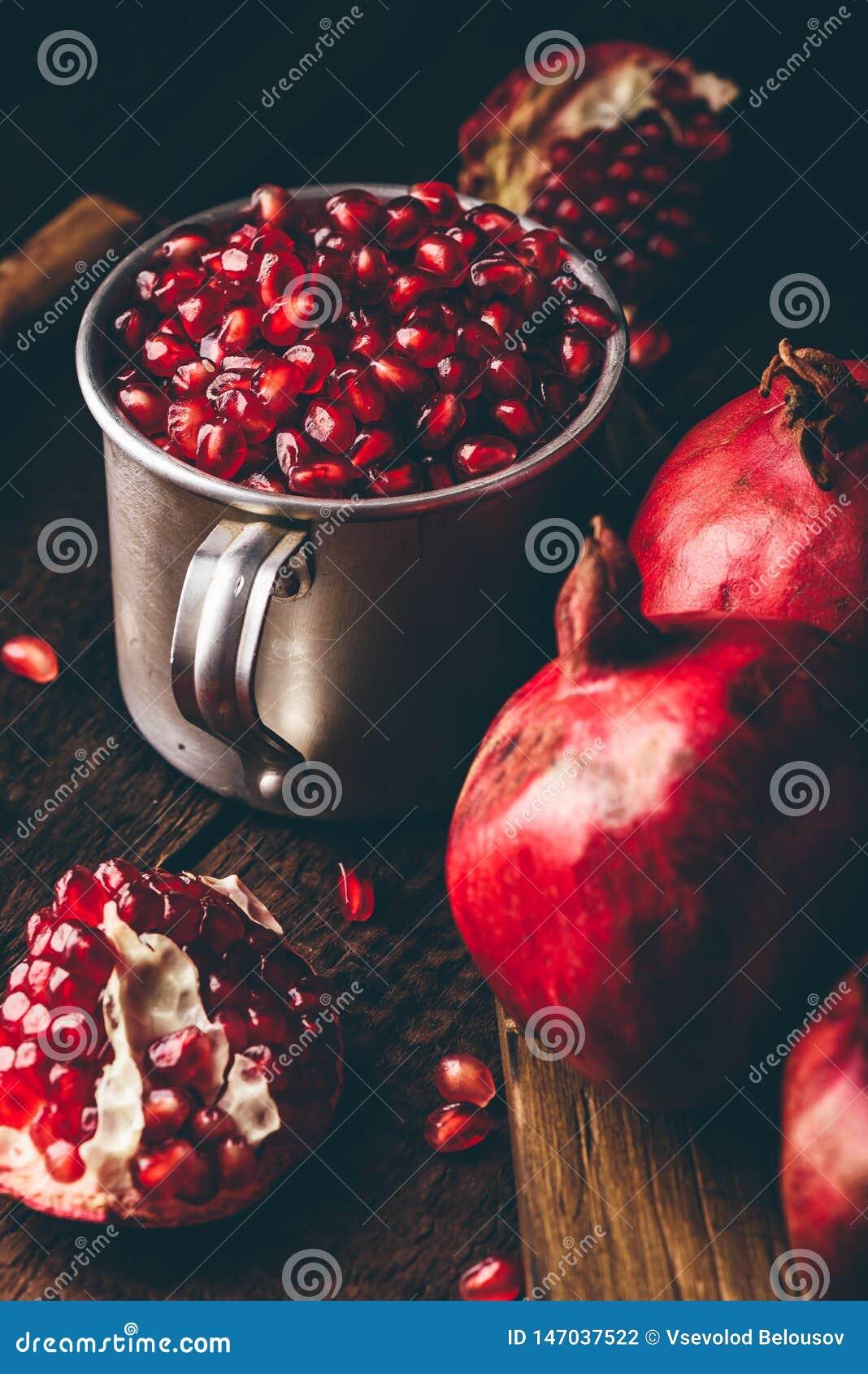 Metal mug full of pomegranate seeds