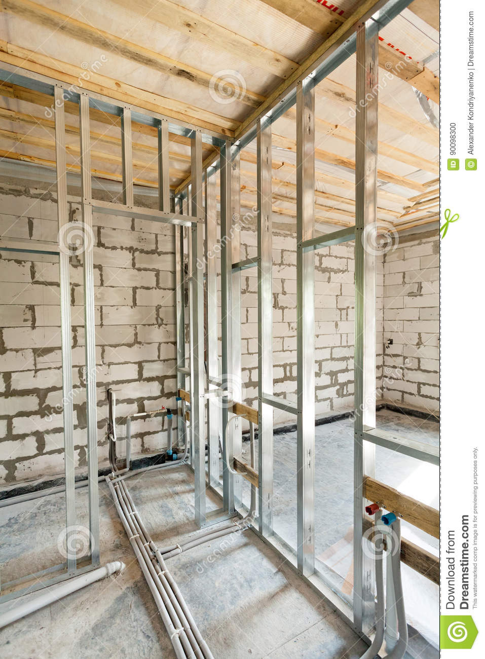 Metal profile frame for plasterboard walls and pipes with valves of a heating system in the house.