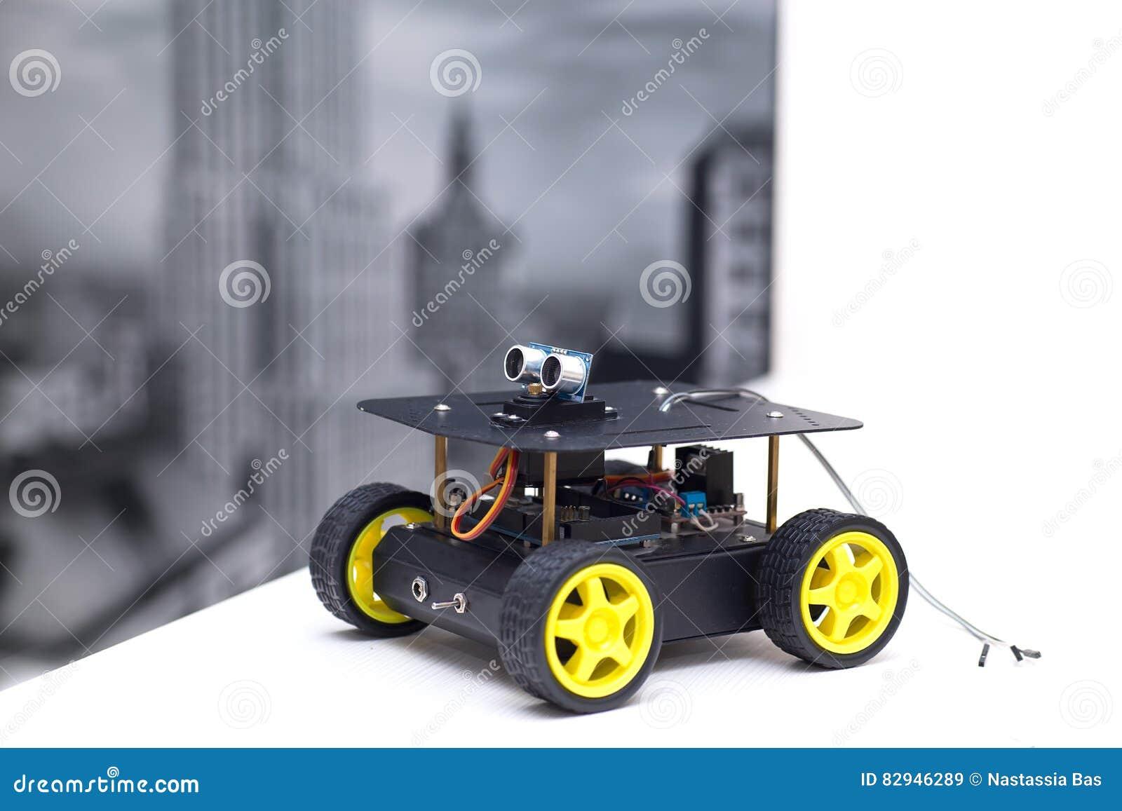 Superb Metal Robot With Yellow Wheels On A White Table Stock Image Interior Design Ideas Tzicisoteloinfo