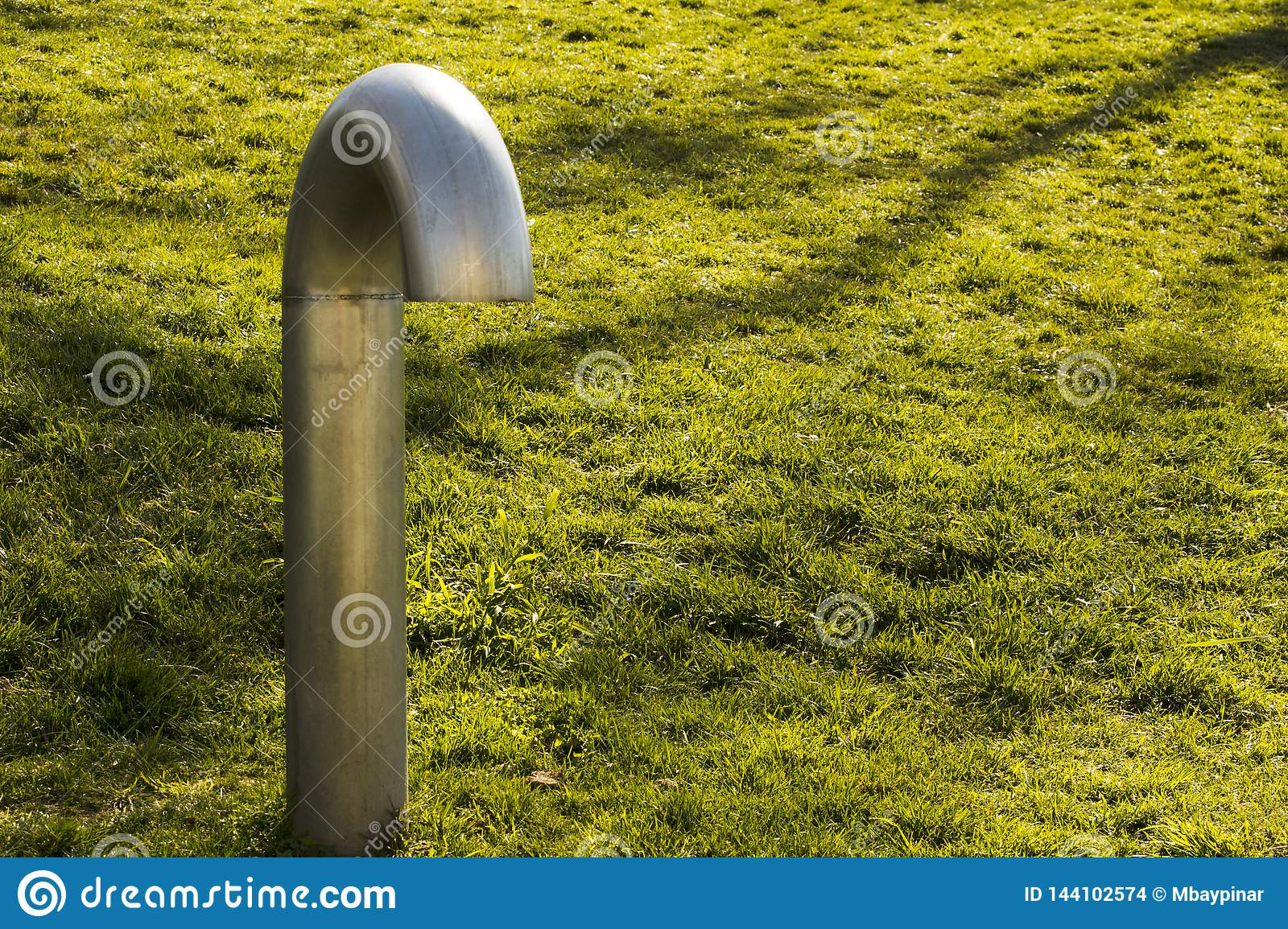 A solitaire ventilation lamp faces down on green grass. Loneliness, submission, bowing to life concepts.