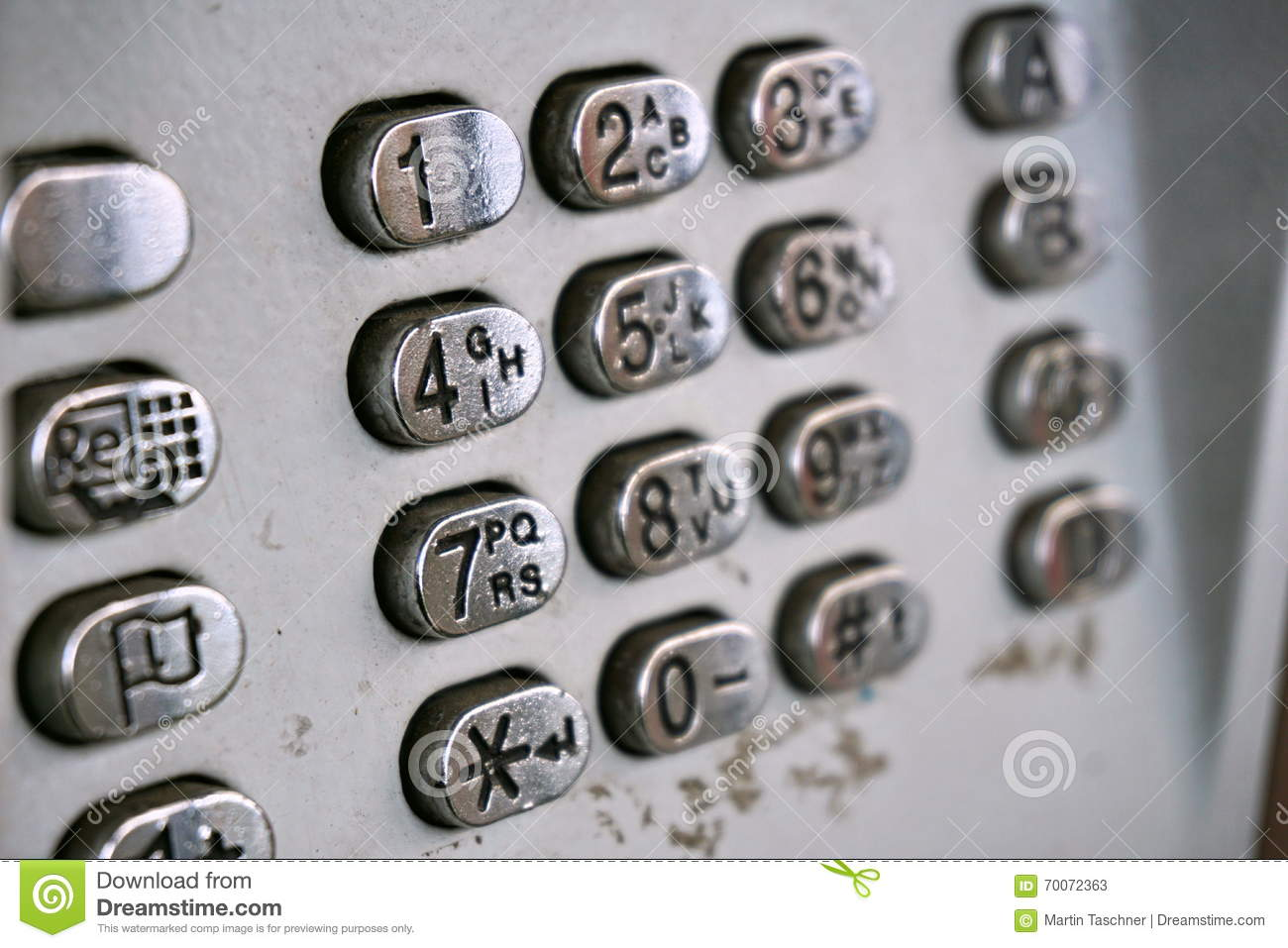 metal telephone dial in the public phone booth with black letters and numbers on the silver