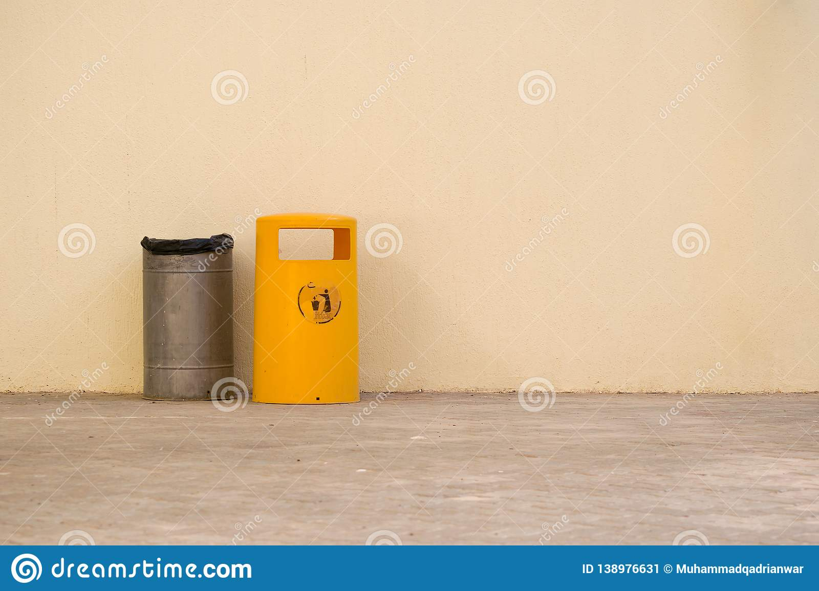Metal trash bin by the side of yellow plastic trash bin. Metallic color metal trash bin by the side of yellow plastic trash bin wih empty space for writing stock image