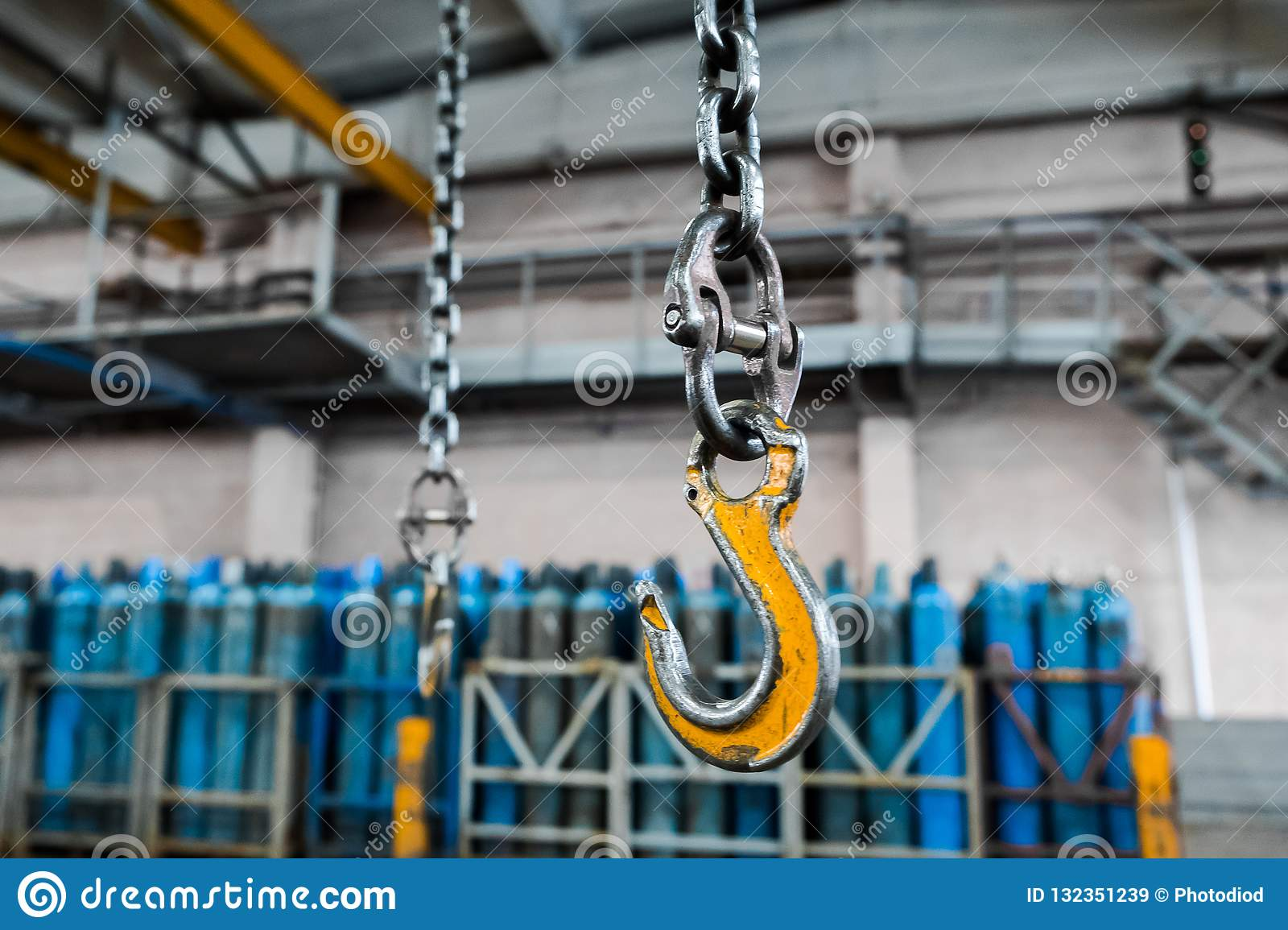 Metallic industrial hook for lifting heavy thing in the factory. Crane hooks on a thick chain inside the factory floor.