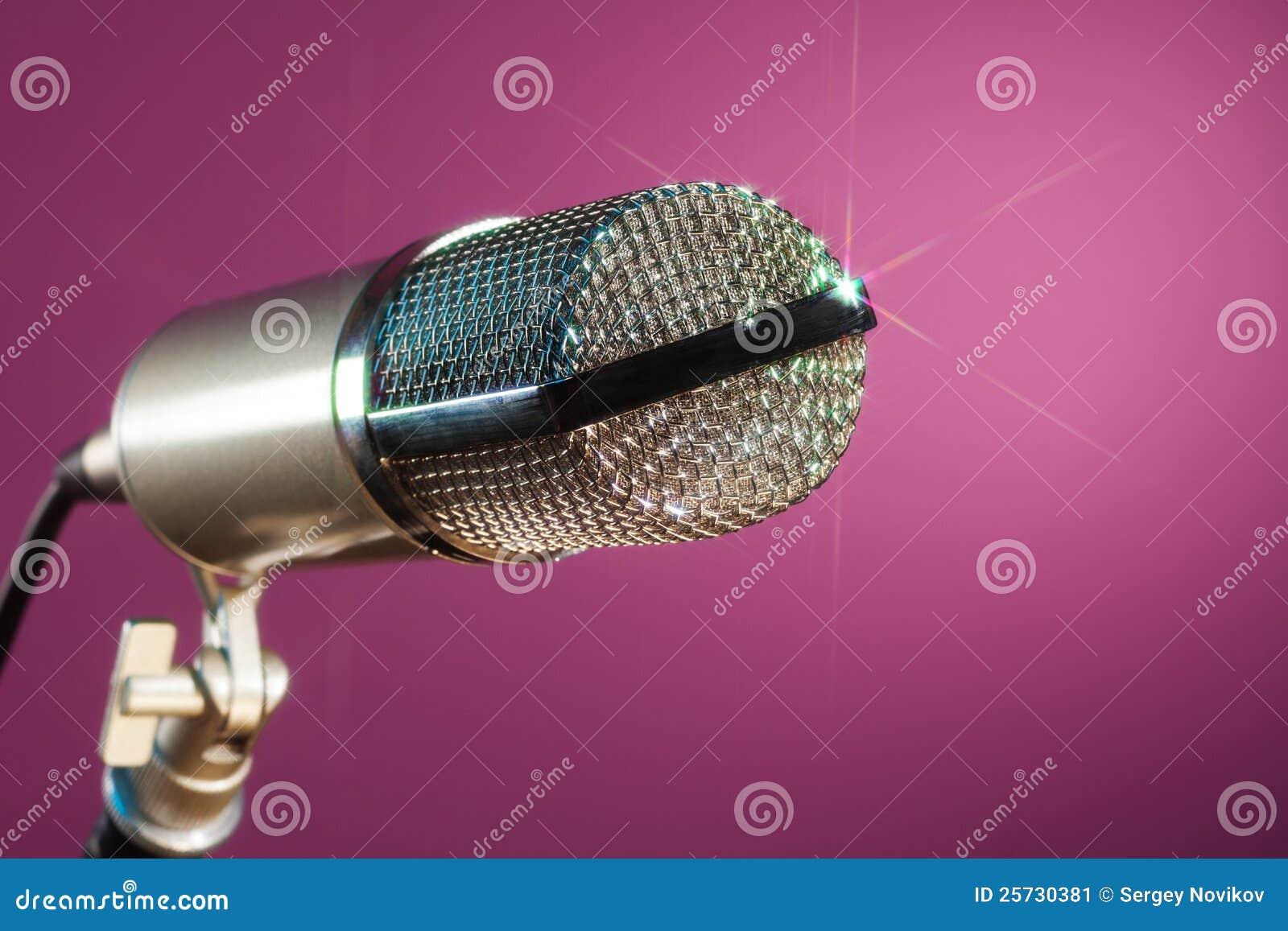 Metallic microphone on pink background