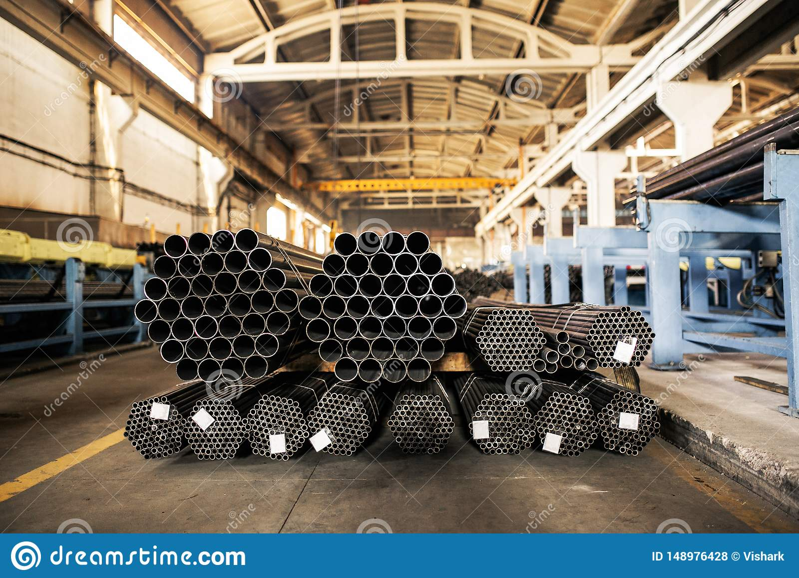 Metallic pipes on warehouse, rows of metal pipes on industrial warehouse. Industrial interior,