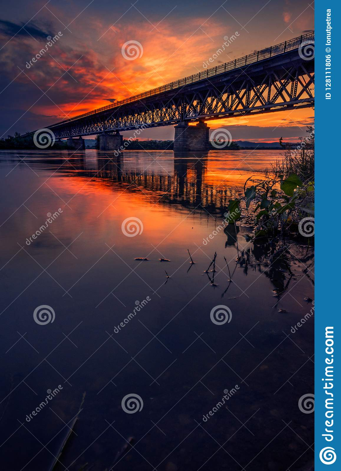 Road bridge crossing a river at sunset with beautiful clouds on