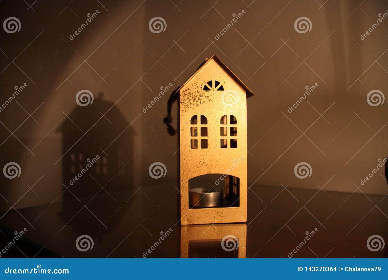 Metallischer Kerzenständer in Form eines Hauses auf dem Tisch am dunklen Abend mit Lampenlicht