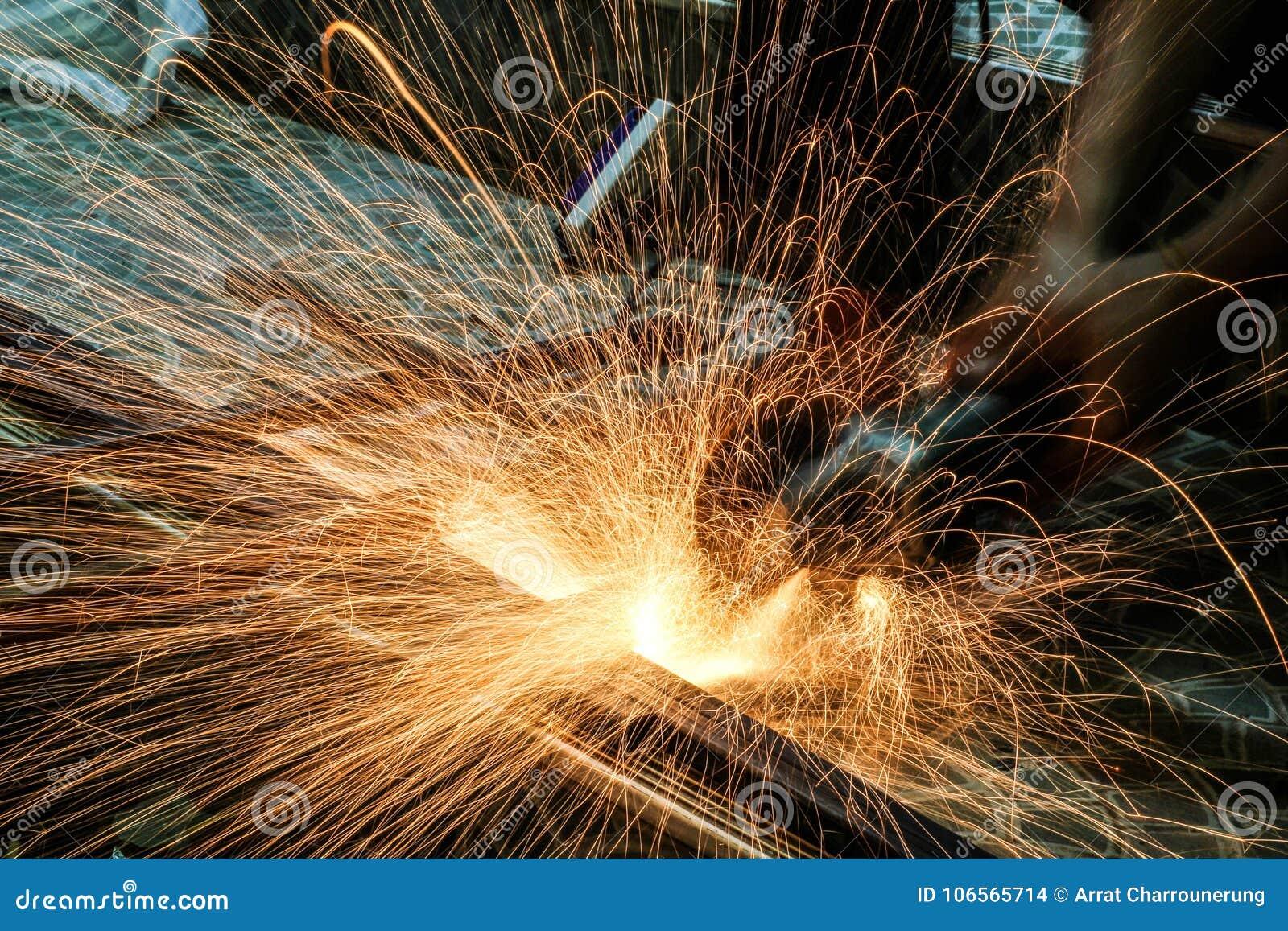 Metallo di taglio dell operaio con la smerigliatrice Scintilla mentre frantumano il ferro