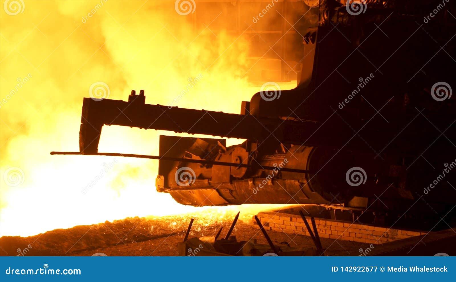 Metallo fuso che versa dal meccanismo speciale, concetto di metallurgia Acciaio fuso che entra nello scivolo metallurgico dietro