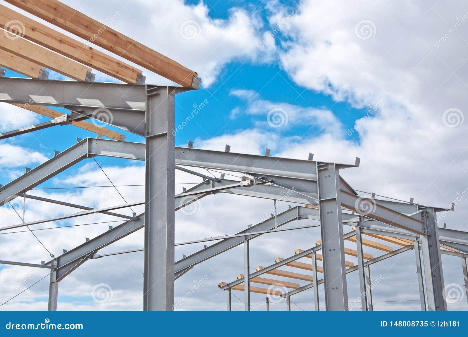 Metallrahmen des Neubaus gegen den blauen Himmel mit Wolken