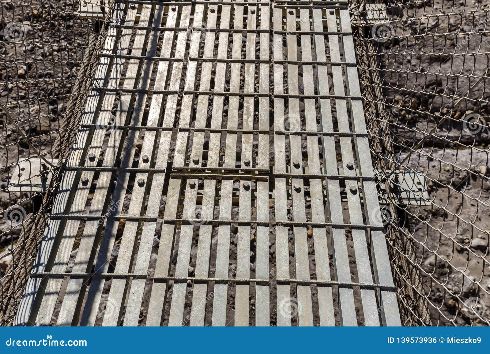 Metallupphängningbro på järnkablar i Nepal