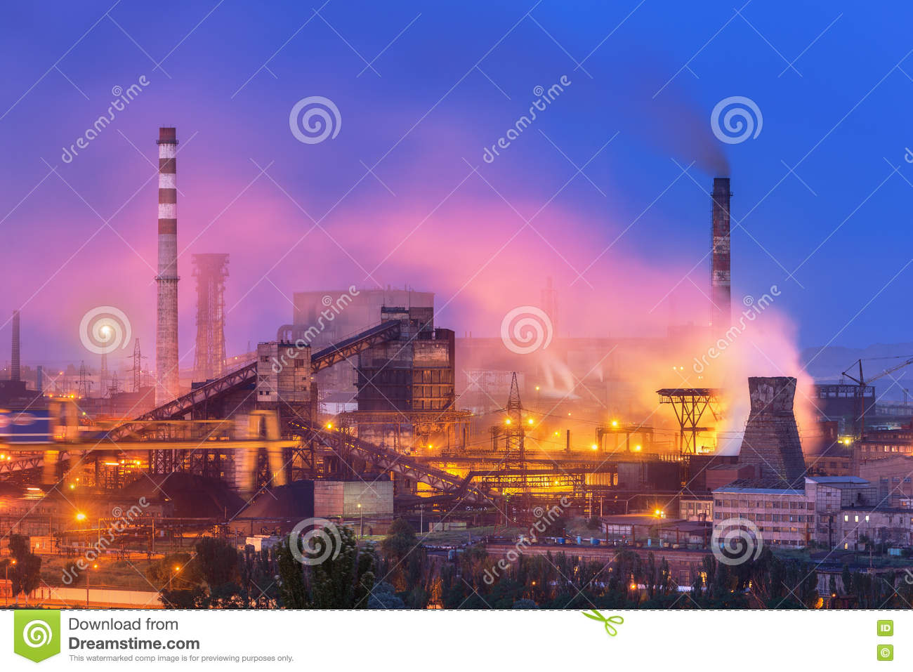Metallurgical plant with white smoke at night. Steel factory with smokestacks . Steelworks, iron works. Heavy industry