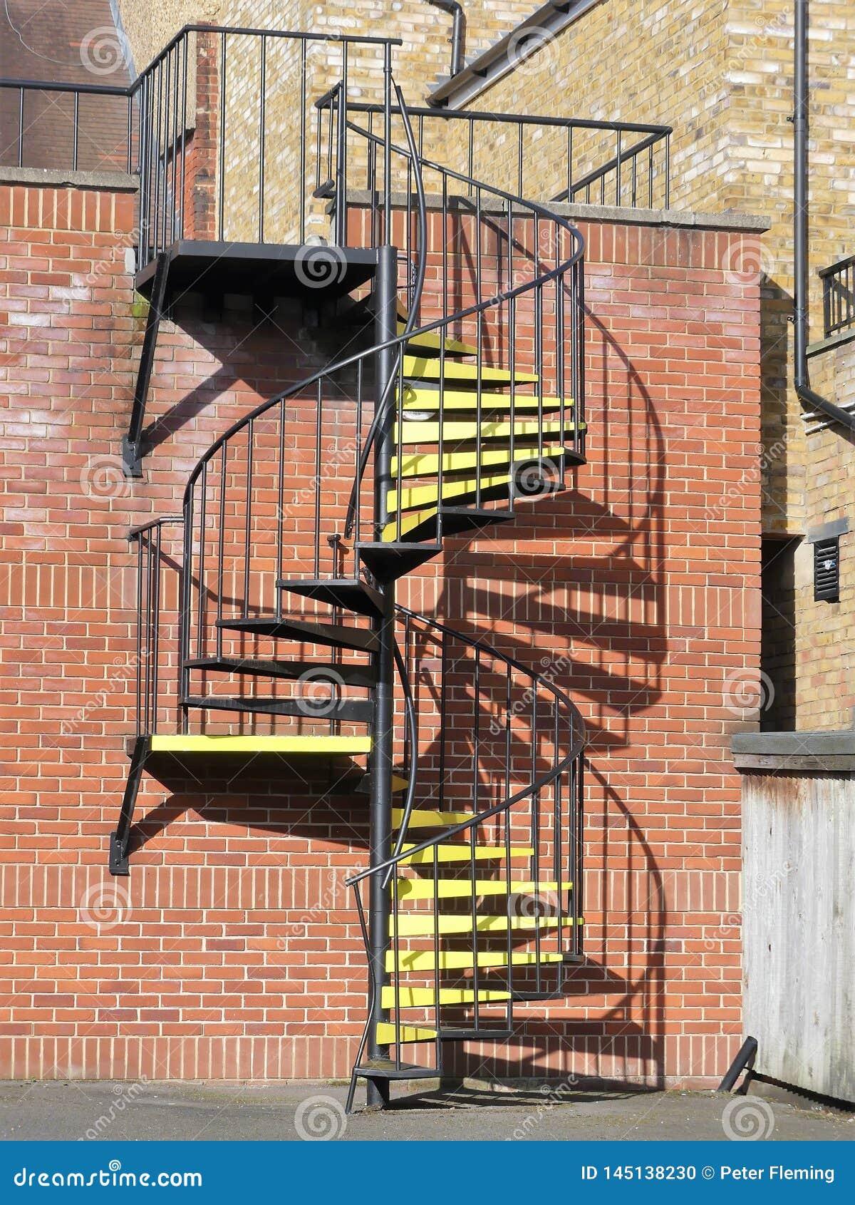 Metallwendeltreppe mit gelben Schritten
