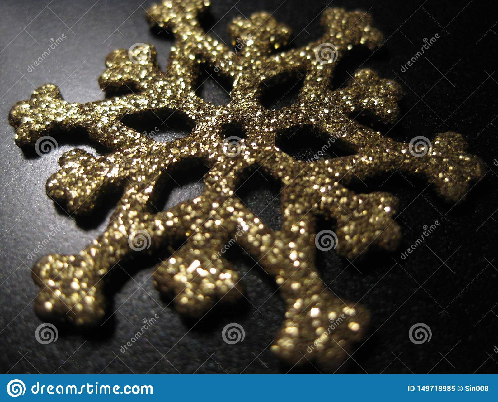 Metalu płatek śniegu z złocistymi cekinami na czarnym tle Złocisty płatek śniegu z błyskotliwością i shimmer Bożenarodzeniowy dek