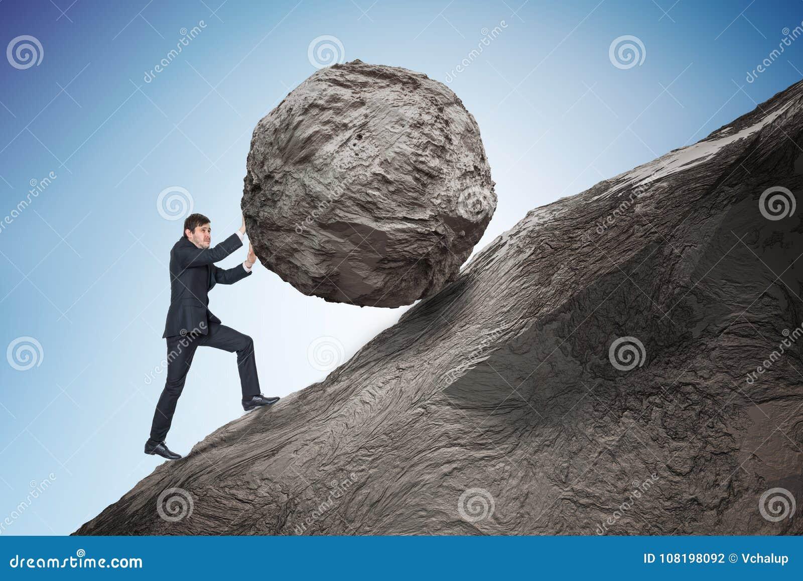 Metaphore de Sisyphus Hombre de negocios joven que empuja el canto rodado de piedra pesado para arriba en la colina
