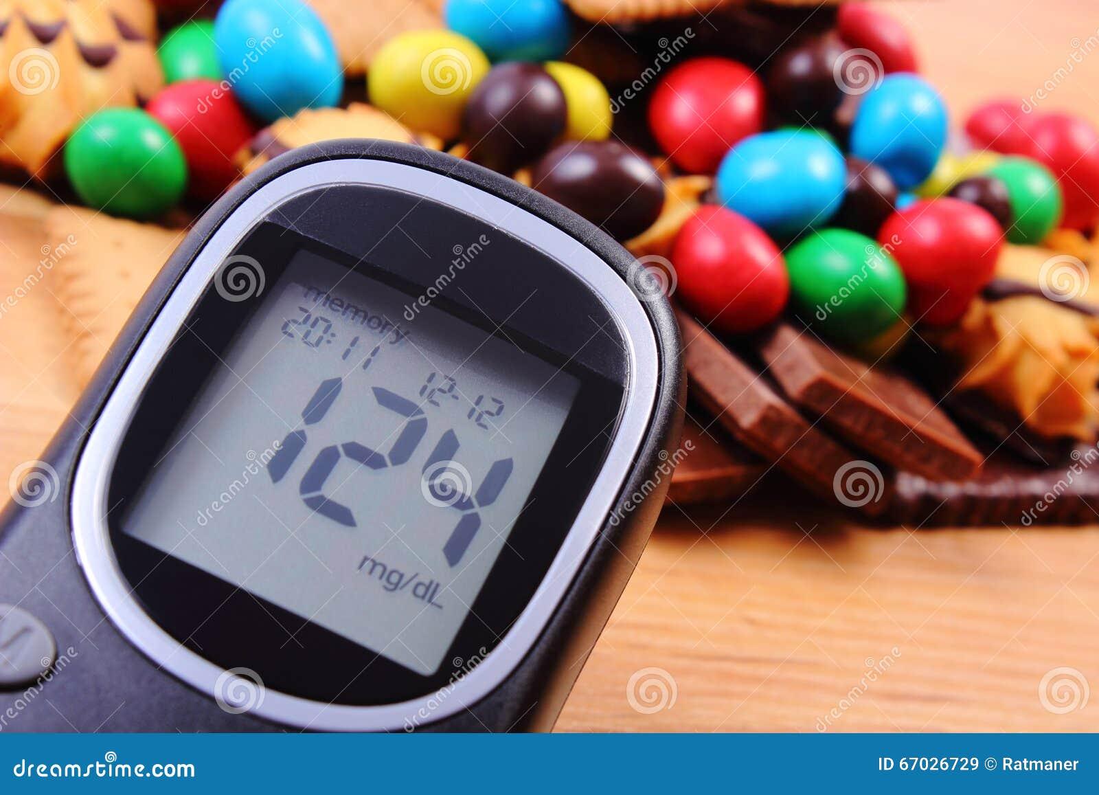 Spuntini Sani E Diabete : Metro del glucosio con il mucchio dei dolci su superficie di legno