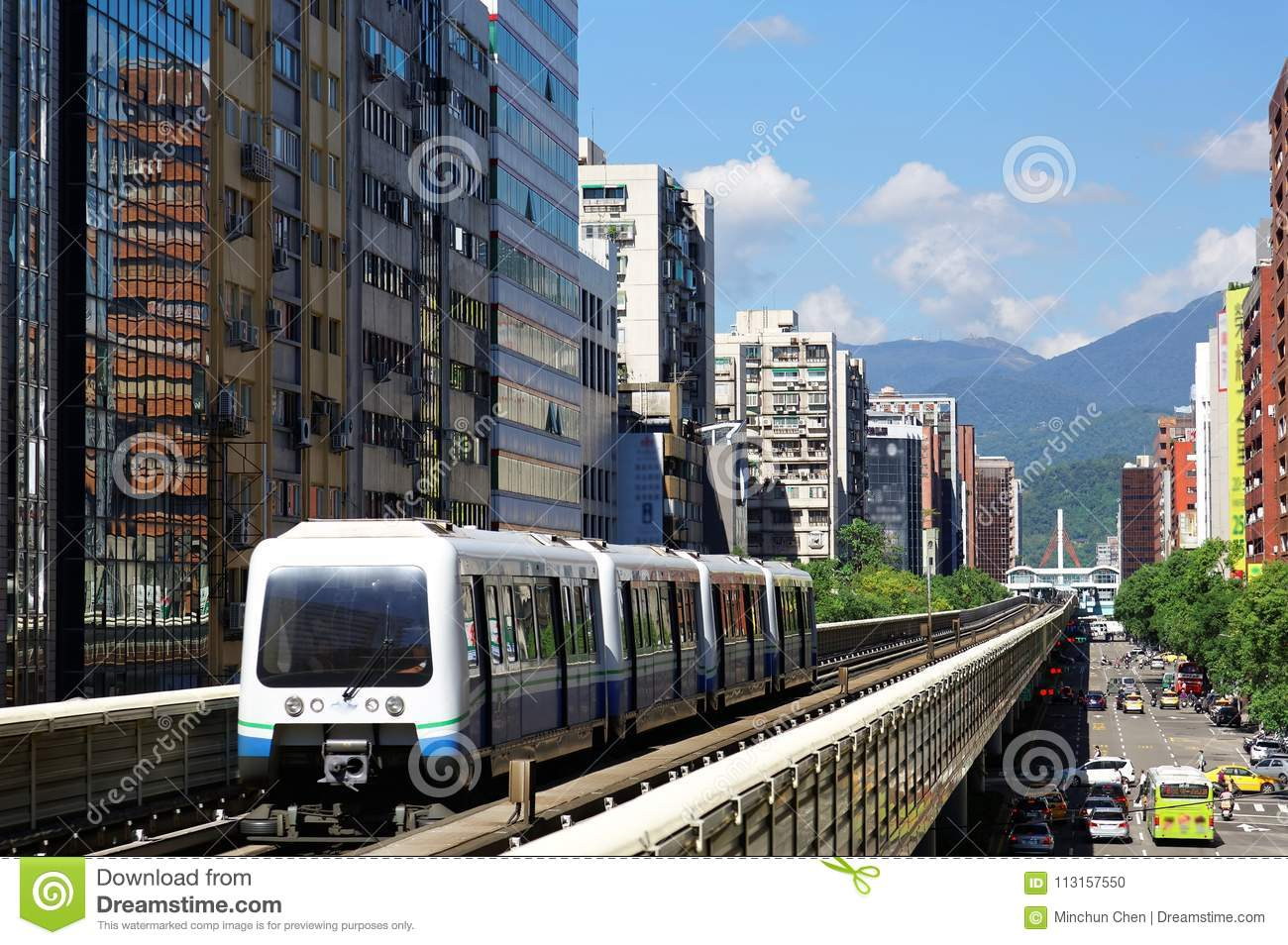 A Metro train travel on elevated rails of Wenhu Line of Taipei MRT System by office towers under blue clear sky