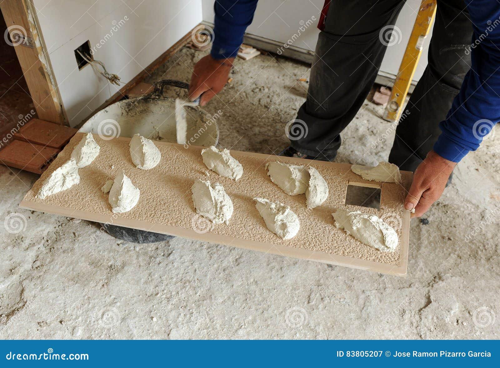 Industrieel Keuken Tegels : Metselaar die cementmortier op tegels zetten stock afbeelding