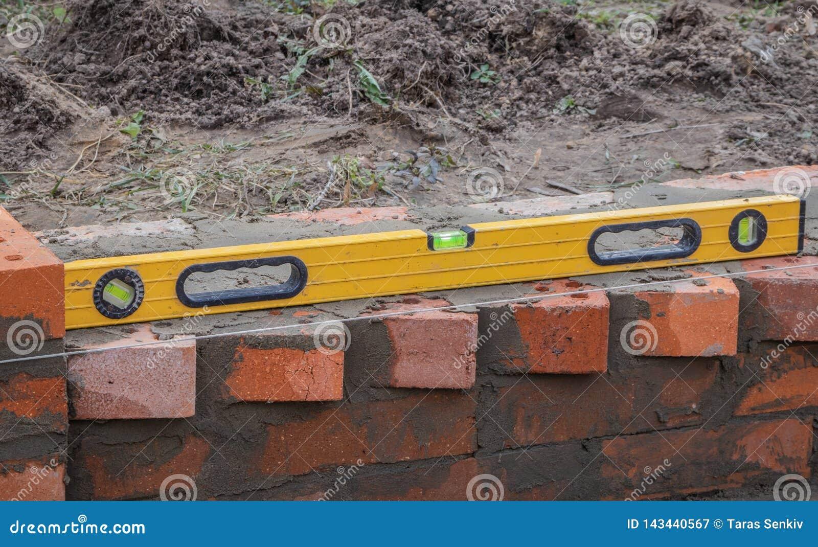 Metselwerk en hulpmiddelen, niveau die, troffel, een huis bouwen